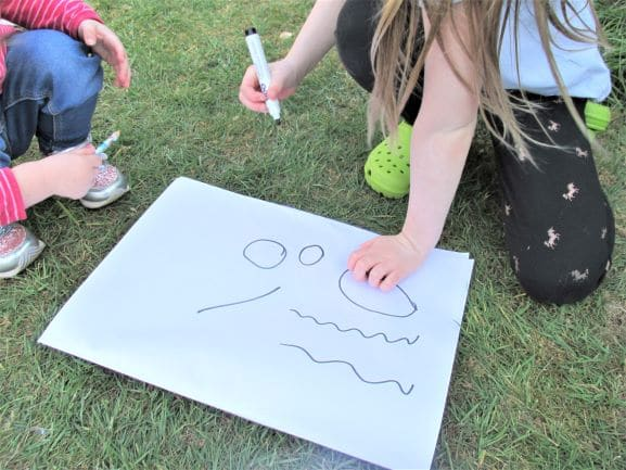 Preschoolers making pre-writing marks on large paper