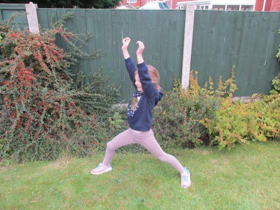 Child doing warrior pose yoga in garden